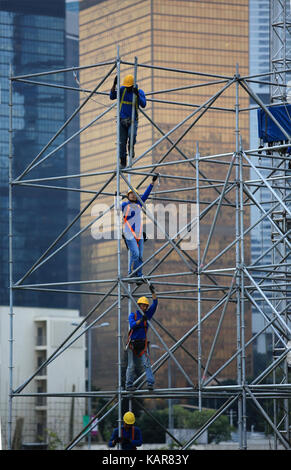 the unidentified workers are scaffolding on the site in the city surrounding by skyscrapers in Central - Stock Photo