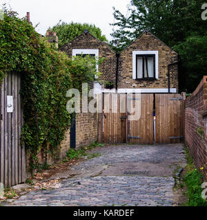 London Greenwich residential area, Driveway with wooden doors and typical small brick cottages - Stock Photo
