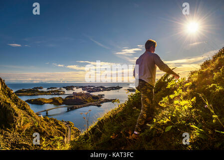 Male hiker going to the top of mount Festvagtinden with views over the village of Henningsvaer on Lofoten islands - Stock Photo