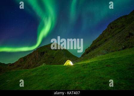 Illuminated tent in the Lofoten islands in Norway with the northern lights overhead (Aurora Borealis) - Stock Photo