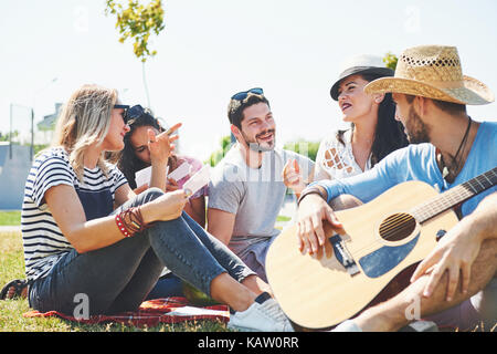 Happy young friends having picnic in the park.They are all happy,having fun,smiling and playing guitar - Stock Photo