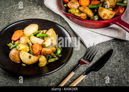 Plate and Skillet with  fried seasonal autumn vegetables (zucchini, potatoes, carrots, beans), on black stone table - Stock Photo