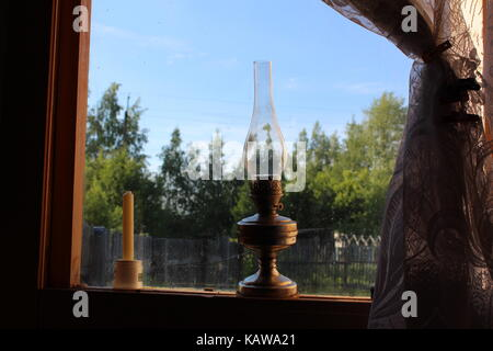 An old-fashioned kerosene lamp stands on a wooden window-sill. - Stock Photo