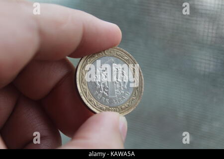 A coin worth 1 Turkish lira between the fingers of the hand. - Stock Photo