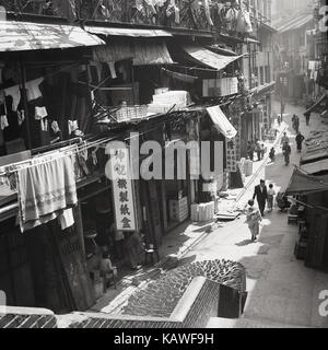 1950s, historical picture from Hong Kong showing a typically busy street with so called 'shophouses', mixing business - Stock Photo