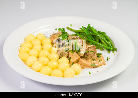 Pork tenderloin with potatoes and wild mushroom sauce and green beans on white plate - Stock Photo
