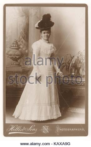 Cabinet card of fashionable, elegant, attractive beautiful Victorian young lady wearing a hat, summer white dress - Stock Photo