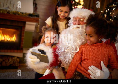 Santa Claus making selfie with three cute girls - Stock Photo