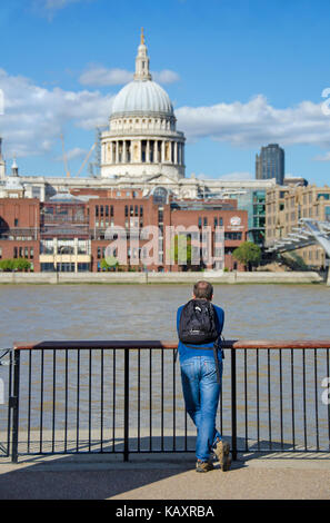 London, England, UK. Man on the South Bank looking across the River Thames towards St Paul's Cathedral - Stock Photo