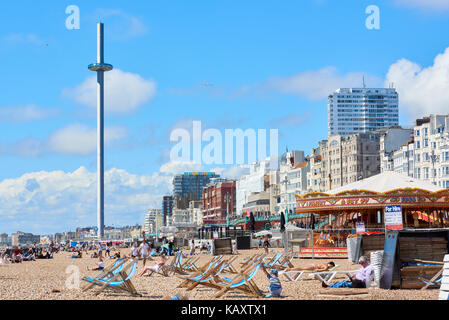 Beachgoers enjoy the sun in Brighton, with British Airways i360 viewing platform in the background. - Stock Photo