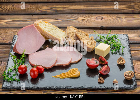 Pieces of cold-boiled, bread, butter, tomatoes, herbs, walnut, mustard. Ingredients for breakfast on black stone - Stock Photo