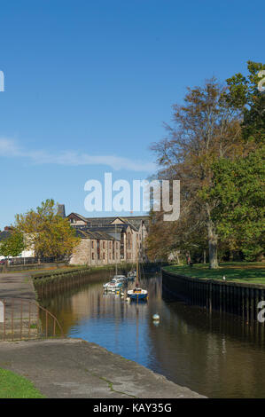 Boats moored in the River Dart beside Vire Island in Totnes, Devon in Autumn with wharf buildings converted to apartments. - Stock Photo