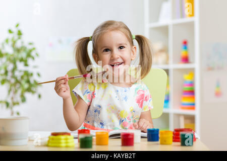 Cute child girl painting picture on home interior background - Stock Photo