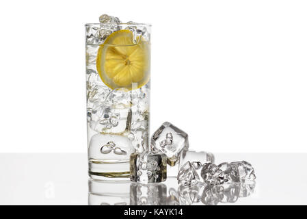 glass full of fresh water with lemon slice and ice cubes on background - Stock Photo
