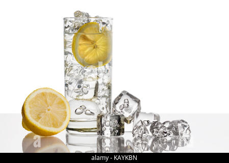 glass full of fresh water with lemon and ice cubes on background - Stock Photo