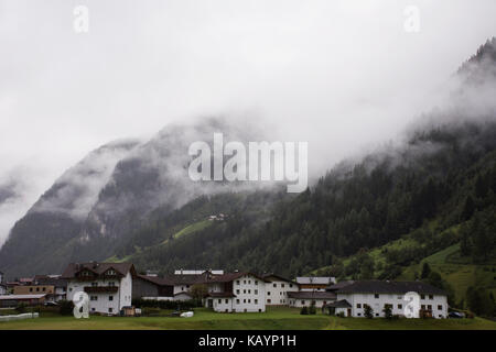 Classic house in Pitztal Valley near Kaunergrat nature park and Kaunertal Valley and Inntal Valley while snowing - Stock Photo