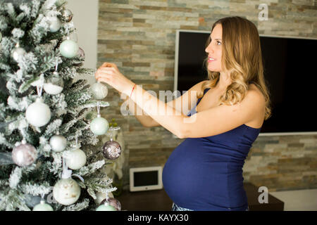 Pretty young pregnant woman decorating the Christmas tree in the room - Stock Photo