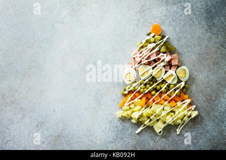 Christmas tree made from salad olivier on a gray slate, stone or metal background. Beautiful Christmas and New Year - Stock Photo