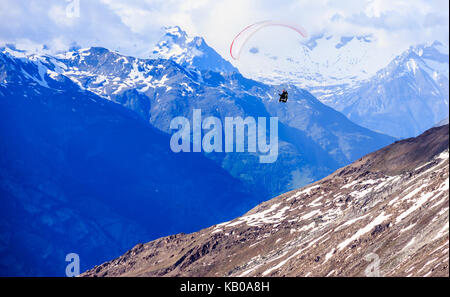 Paraglider flying over mountains in the summer day sky, Paragliding recreation sport leisure activities. Swiss Alps - Stock Photo