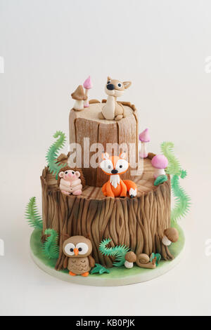 Enchanted forest woodland themed fondant cake with a hedgehog, deer, owl, fox, snail, tree trunk, ferns, mushrooms - Stock Photo