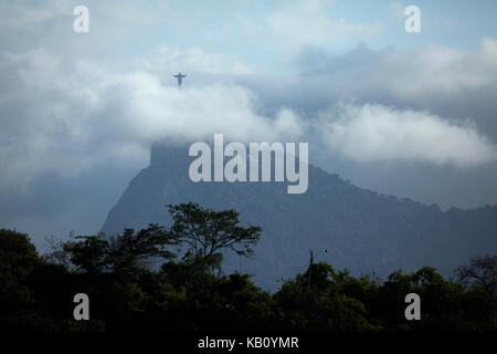 Christ the Redeemer in the clouds atop Corcovado, seen from Niteroi, Rio de Janeiro, Brazil, South America - Stock Photo
