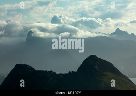 View across Guanabara Bay to Christ the Redeemer in the clouds atop Corcovado, Rio de Janeiro, Brazil, South America - Stock Photo
