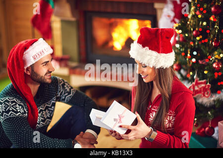 Smiling girl opening Christmas gift from guy - Stock Photo