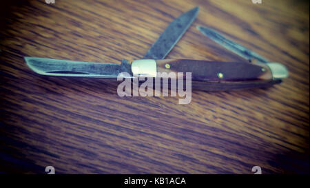 A vintage grungy knife blades on a table. - Stock Photo