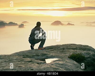 Tourist sit on peak of sandstone rock and watching into colorful mist and fog in  morning valley. Sad man. Man sit. - Stock Photo