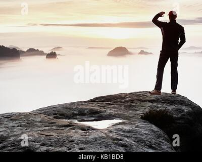 Man stands alone on the peak of rock. Hiker watching to autumn  Sun at horizon . Beautiful moment the miracle of - Stock Photo