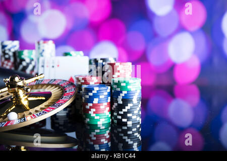 Casino concept. Roulette, chips, cards and dice on colorful bokeh. - Stock Photo