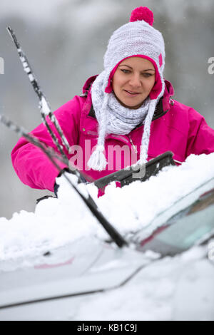 girl cleaning snow car from, winter time - Stock Photo
