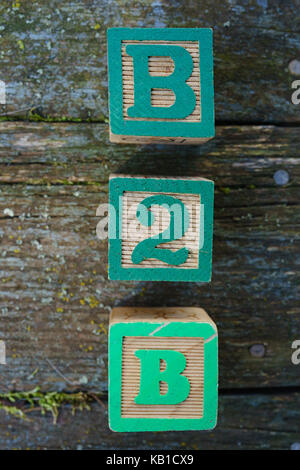 Children's wooden toy blocks spelling B2B on a weathered wooden background. - Stock Photo
