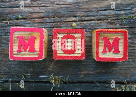 Children's wooden toy blocks spelling MOM on a weathered wooden background. - Stock Photo