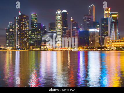 View of Singapore Downtown Core reflected in a river at night - Stock Photo