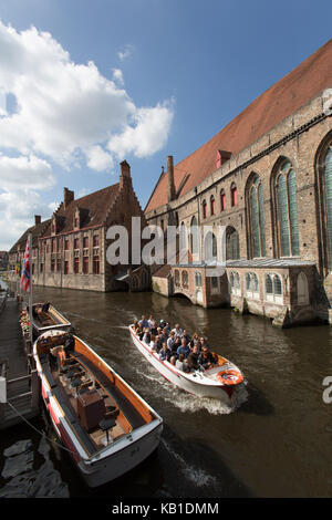 City of Bruges, Belgium. Tourists on a canal boat trip, with St John's Hospital on the right of the image.