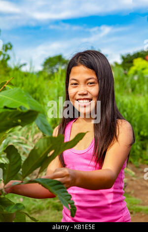 Waist up portrait of a twelve-year old Filipino girl with long, black hair and a nice, toothy smile living in Ormoc - Stock Photo
