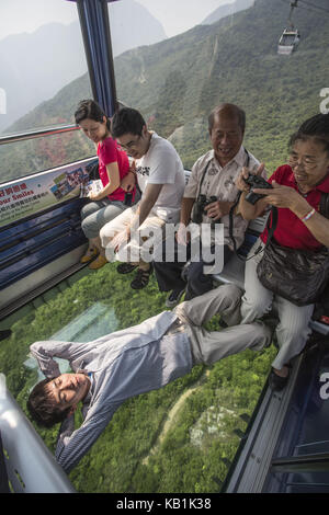 Tourists in a cable car, Lantau Iceland, Hong Kong, - Stock Photo