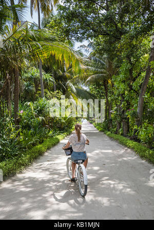 Young girl bicycling under palm trees on a tropical island. Maldives. - Stock Photo
