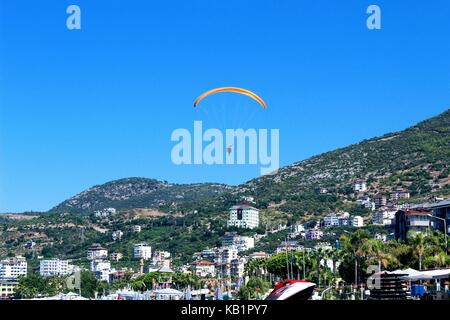 Paraglider landing in a special zone at Cleopatra Beach in Alanya (Turkey). - Stock Photo