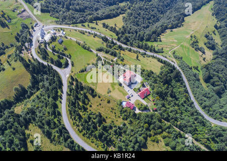 Aerial view over mountain road going through forest landscape - Stock Photo