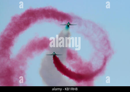 A British Aerospace Hawk of the Saudi Hawks aerobatic team barrel-rolls around another during an air display - Stock Photo