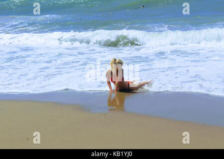 July, 2017 - A woman in a red swimsuit in the surf on the seashore at Cleopatra Beach (Alanya, Turkey). - Stock Photo