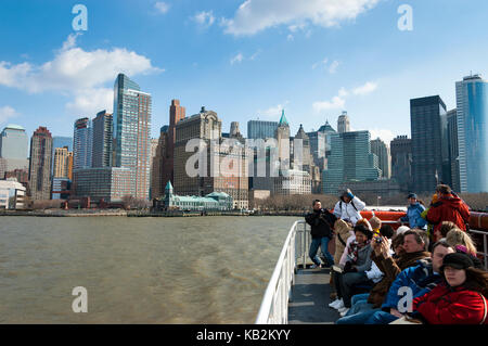 Tourists in a ferry departing from the Port of New York, Battery Park, in a ferryboat tour to Liberty Island, New - Stock Photo