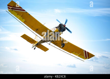 aircraft in red and orange against blue sky - Stock Photo