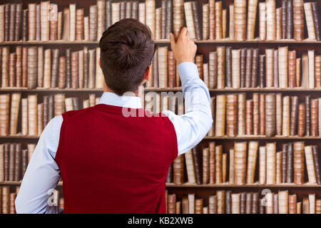 Male student take a book from the shelf in the library - Stock Photo