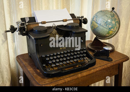 ... Antique typewriter, globe and stapler on a desk - Stock Photo - Antique Typewriter, Globe And Stapler On A Desk Stock Photo