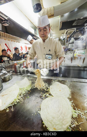 Japan, Kyushu, Hiroshima, restaurant, cook while preparation of Okonomiyaki, - Stock Photo