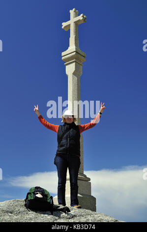 Spain, Way of St. James, pilgrim while arriving on stone cross of the cape Fisterra in Galicia, - Stock Photo