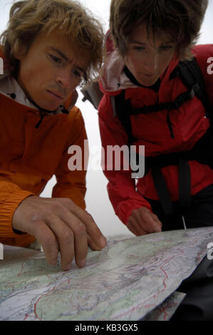 Mountain Hiker while reading the hiking map, - Stock Photo